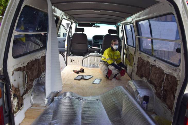 Stuffing the voids with insulation during our campervan conversion