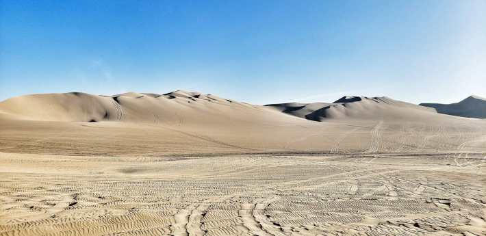 Huacachina tour - picture of the Huacachina sand dunes with a blue sky and tire marks in the sand