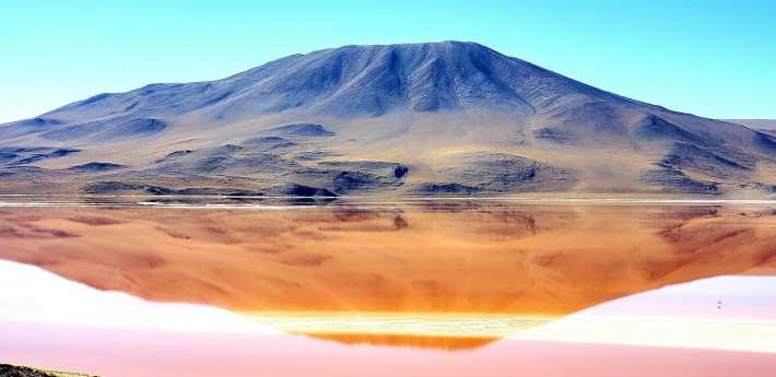 A mountain is reflected in a red tinted lake