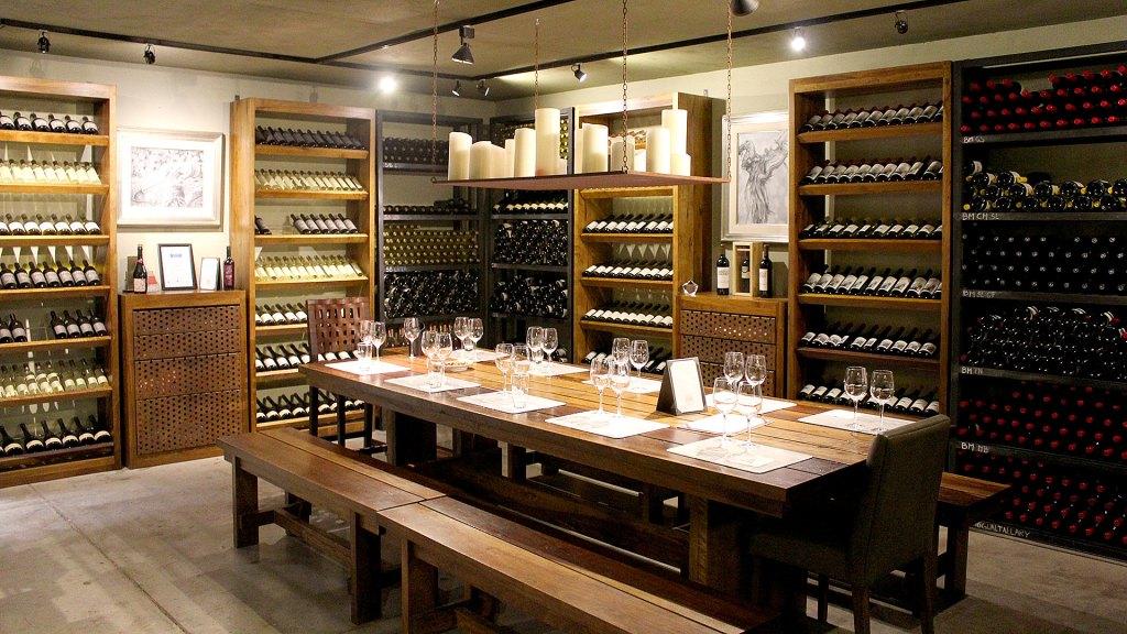Sótano de la bodega Susana Balbo, con almacén de vinos y mesa de degustación