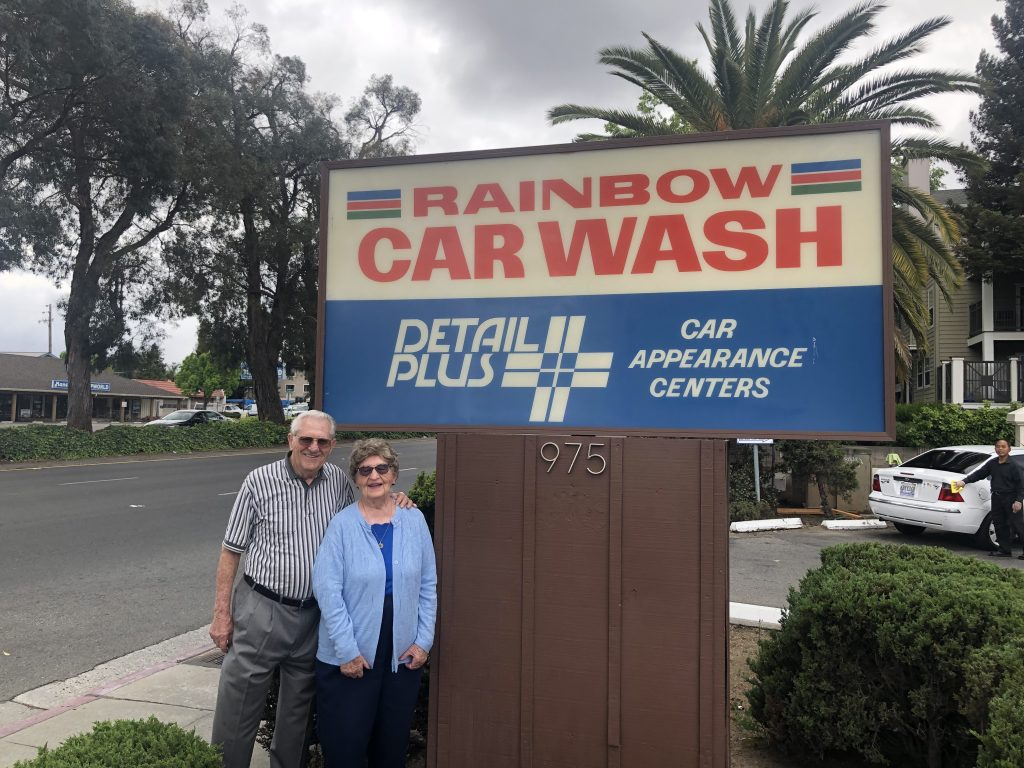 "Ilah and Earl Schmieding pose for a photo under a sign that reads ""Rainbow Carwash Detail Plus Car Appearance Centers"""