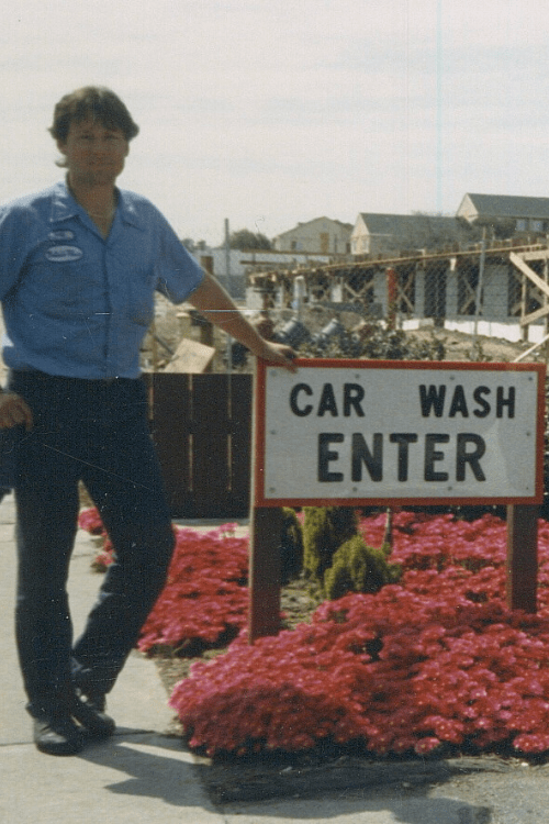 Old photo of manager next to car wash sign at Rainbow Carwash Detail Plus in Sunnyvale, California