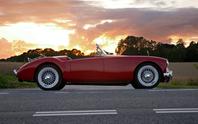 old red car with sunset