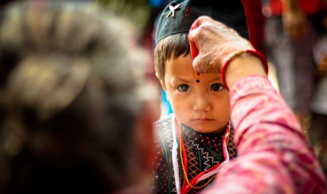 Little kids receives tika put on his forehead by an elderly woman in Suryabinayak, Bhaktapur.