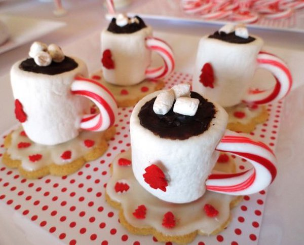 Pretty looking tea Christmas cupcakes. The mini cakes have been made to look like small mugs of hot choco with marshmallows on top and candy canes as the mug handle.