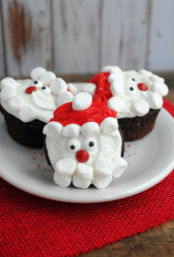 Santa inspired Christmas cupcake. The chocolate cupcakes are designed to have Santa's cartoon face on top with the use of red and white icing.