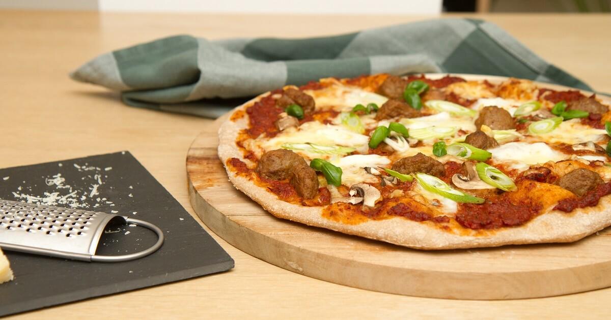 Pizza med kjøttboller vårløk og pizzasaus av soltørkede tomater