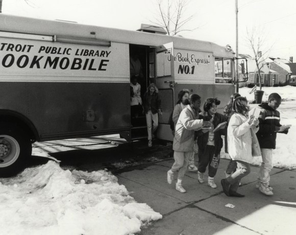 Children in an undated historic black and white photo exitt he Detroit Public Library Bookmobile.