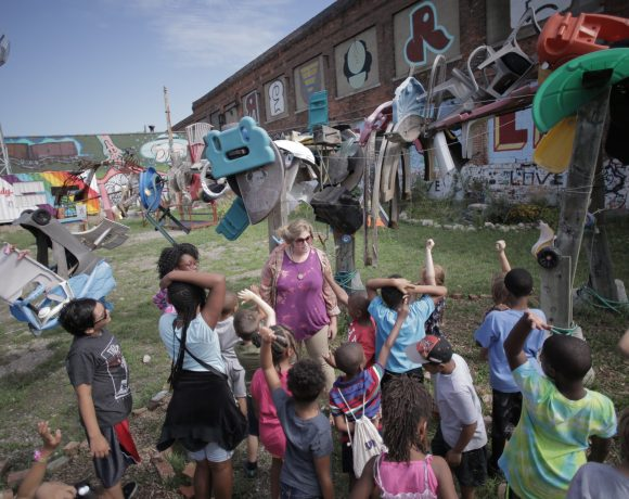 A group of kids learns next to a dinosaur sculpture made of found objects at the Lincoln Street Art Park in Detroit. It's the site of the forthcoming Dreamtroit redevelopment project.