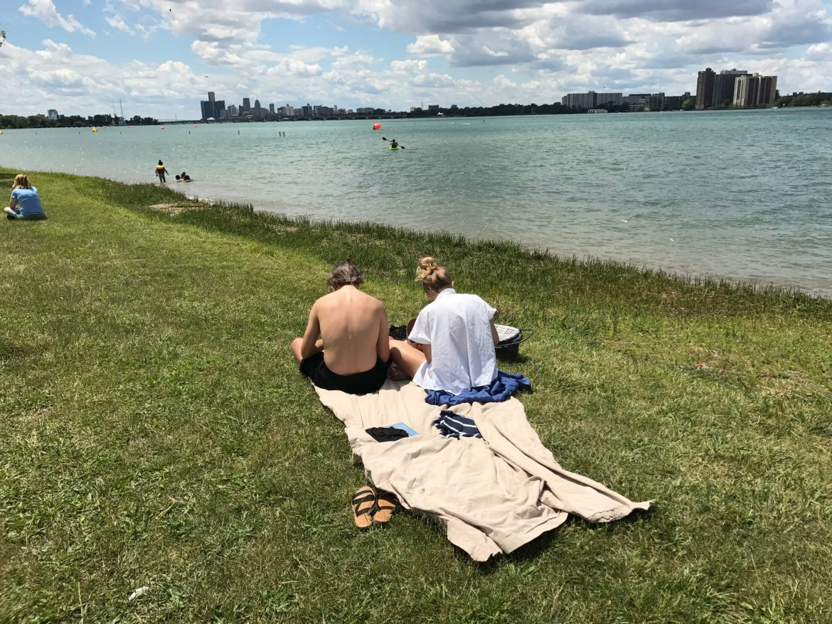 Two people sitting on the grass near the water and belle isle. Michigan proposal 1 would change how state funding is spent on park lands