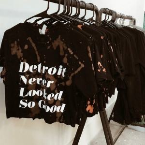 """The Aesthetic Method, rack of black, bleach dyed shirts that say """"Detroit Never Looked So Good"""""""