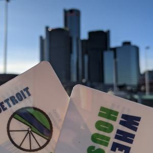 Wheelhouse Detroit, close-up picture of of two Wheelhouse Detroit gift cards being held in front of the renaissance center in Detroit