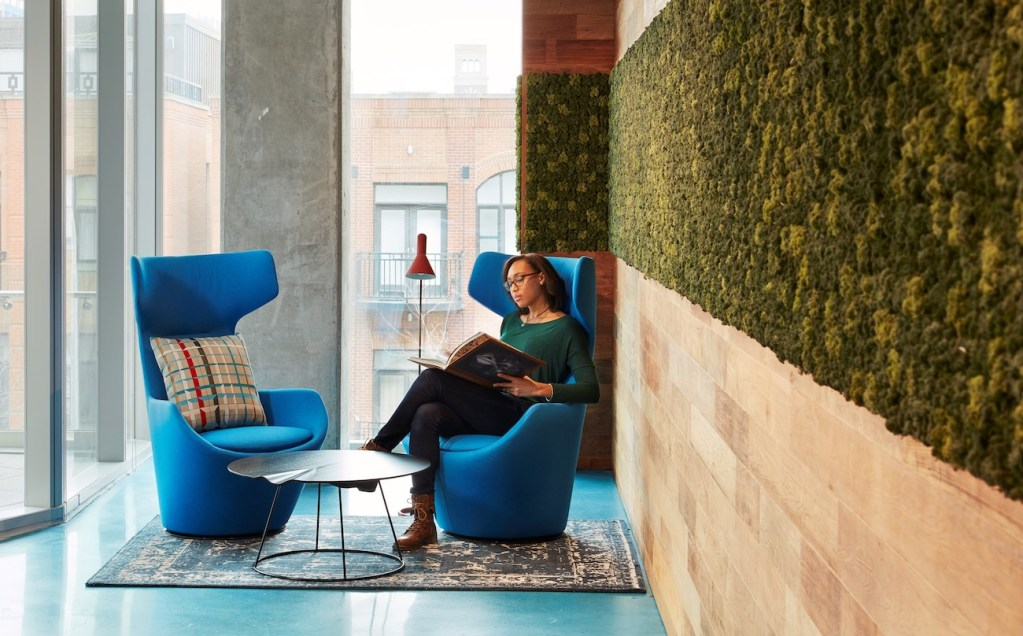 Woman reading in semi-private seating area in an office next to windows and a living wall