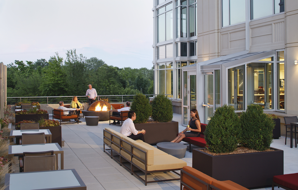 outdoor space design at an office showing seating areas and workers