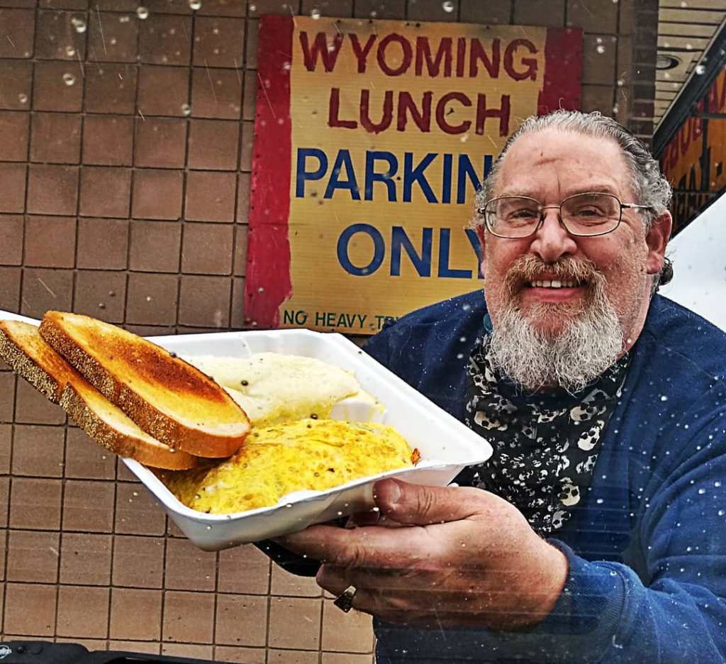 Shows man posing with food