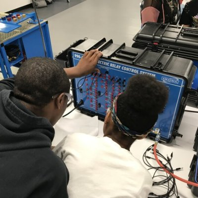 A University Prep Science & Math High School student get a close look at working on electric relay control systems in LIFT's Detroit Learning Lab.