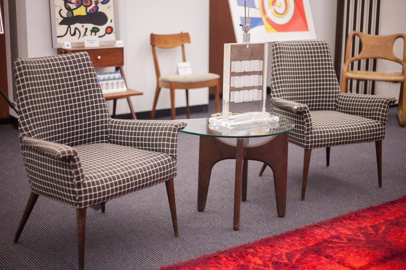 Vignette featuring a pair of Paul McCobb 3049 Chairs alongside an Adrian Pearsall side table with a Lucite lamp. The McCobb chairs were one of the top selling lots of the sale.