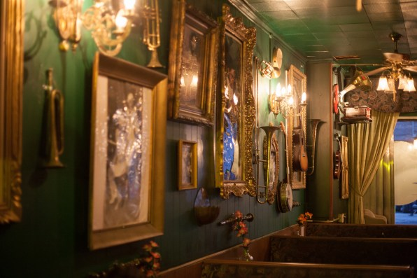 Musical instruments and photos in elaborate frames line the walls at the speakeasy. Photo by Stephanie Hume