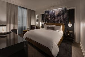A GUEST ROOM FEATURING A TAPESTRY BACKDROP FROM DETROIT ARTIST OUZI. RENDERING FROM APARIUM HOTEL GROUP