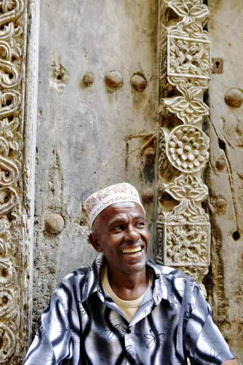 Smilende mann foran utskåret dør på Lamu