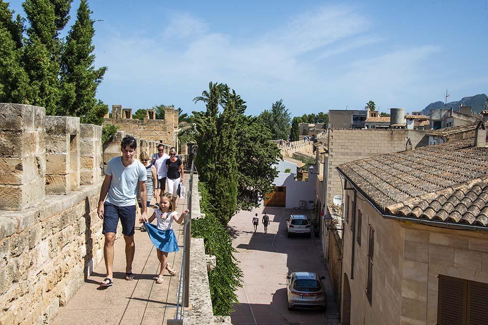 Turister går på bymuren i Alcudia