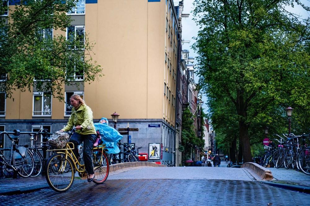 Syklist svinger rundt et hjørne i Amsterdam med en baby bakpå