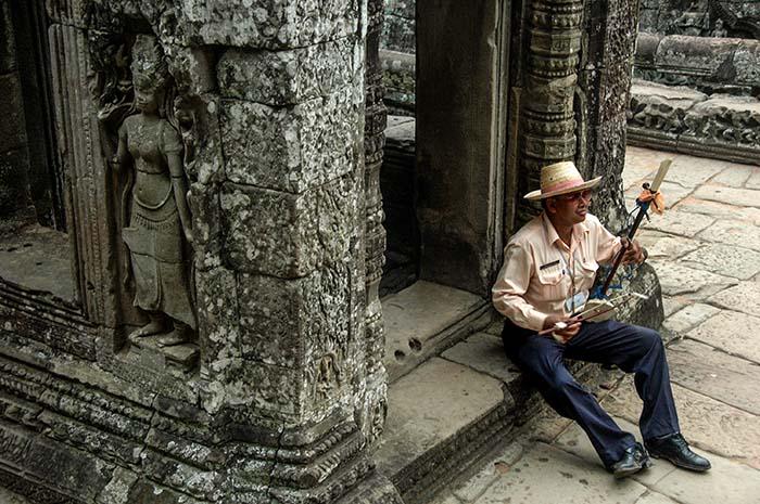Guide spiller tro i Angkor-tempelet Bayon i Kambodsja