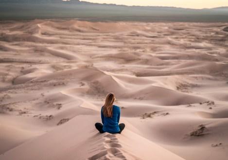 Femme méditant dans les dunes du désert de Gobi, voyage en Mongolie avec Nirvatravel