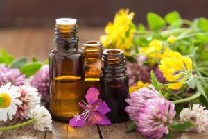 flacons en verre d'huiles essentielles avec des fleures autour