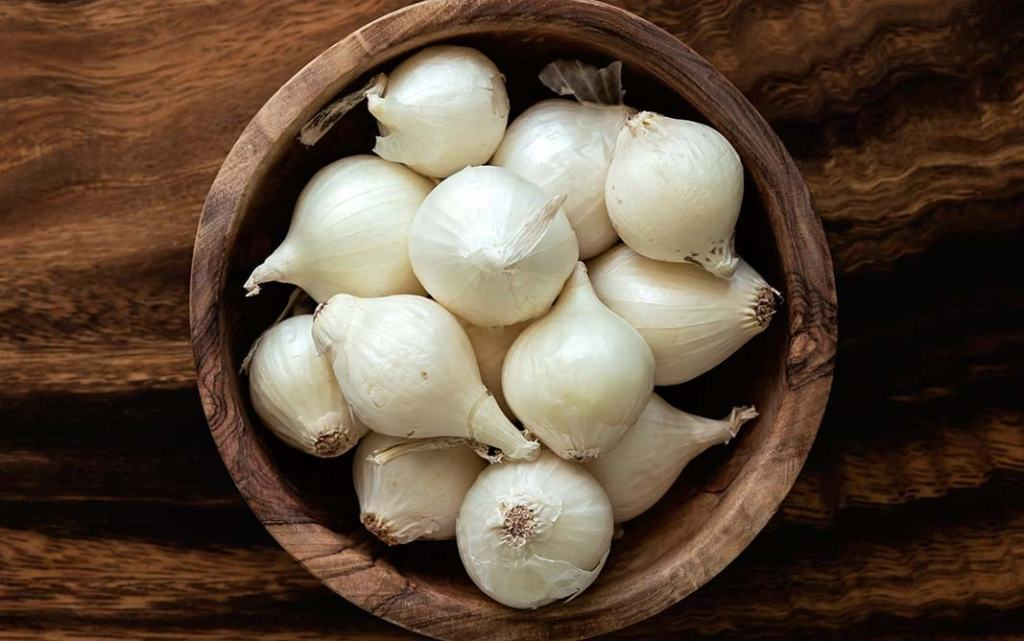 downward shot of wooden bowl filled with Pearl Onions