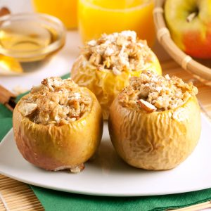 Three baked apples stuffed with bread pudding, topped with nuts and cinnamon.