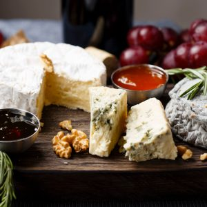 A beautiful rustic wooden cheese board, served with nuts, herbs, jam and grapes