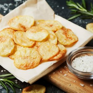 Homestyle potato chips served on craft paper with a small dish of kosher salt