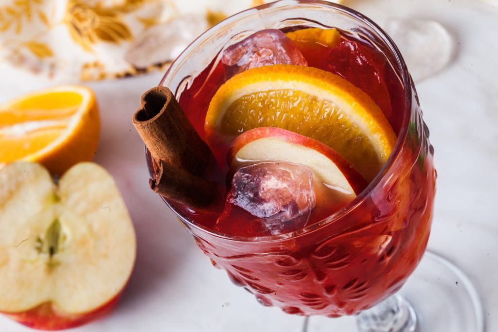 St. Supéry Warm Rose and Brandy Cocktail on the rocks in a goblet, garnished with an apple slice, orange slice and cinnamon sprig