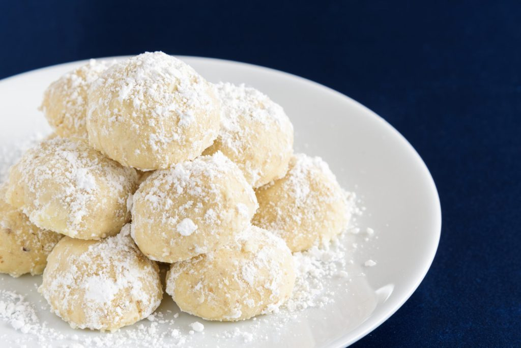 Holiday Russian Tea Cake cookies, dusted with powdered sugar and ready to eat on a white serving plate