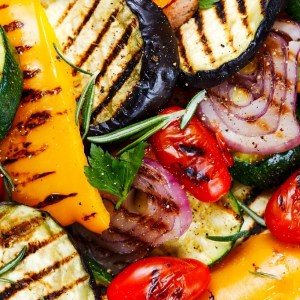 Grilled vegetables. On cutting dark board background.
