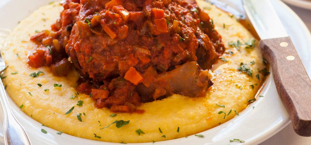Braised beef over polenta in a white bowl