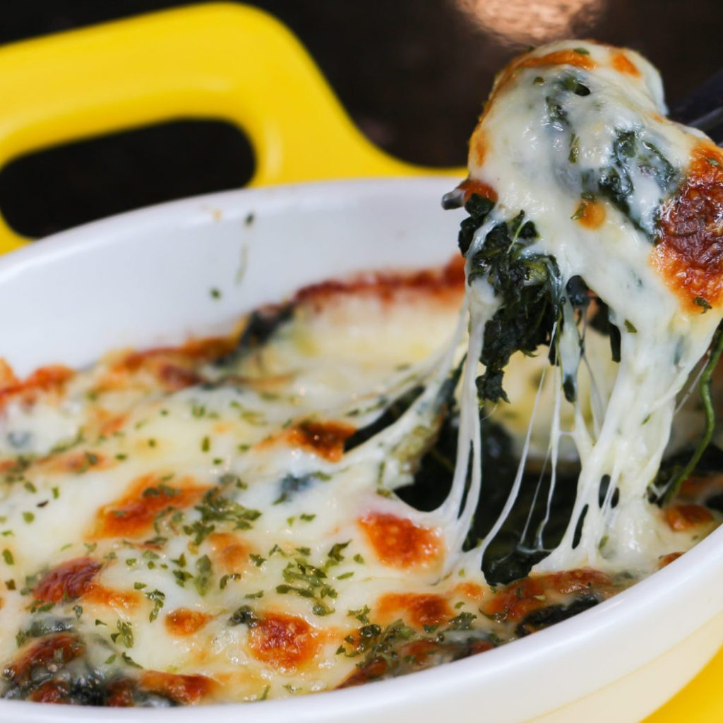 Eating Baked spinach with cheese in yellow dish on black table