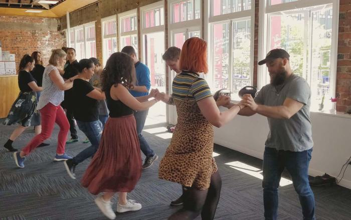 Optima Workshop team members enjoying a salsa class at work