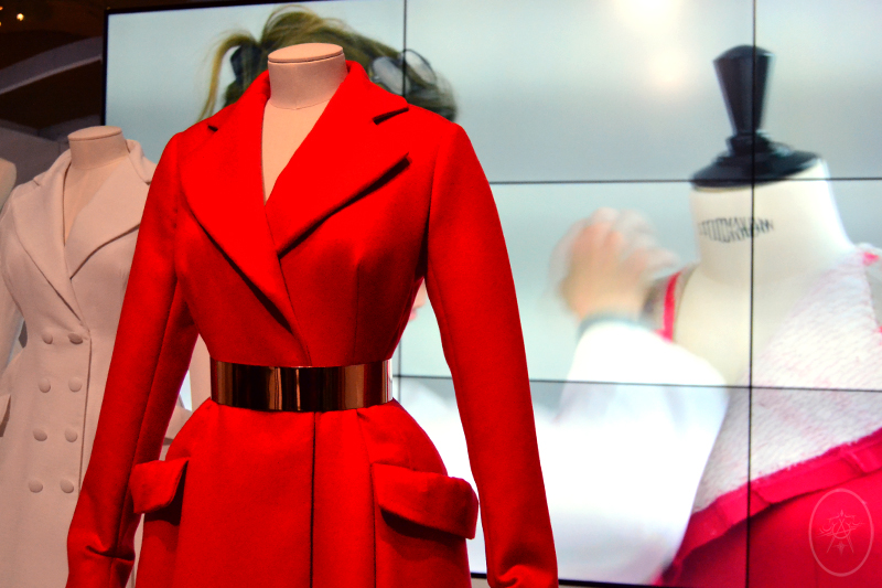 Red Dior coat toile accompanied by behind-the-scenes video of its construction, at NGV International, Melbourne, Australia