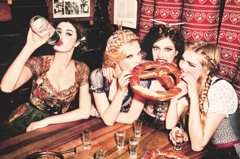 Three models in dirndls tuck into a giant pretzel while another drinks from a bottle of vodka, by Ellen Von Unwerth
