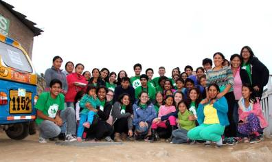 Peru B participants pose with children and parents from Hijos de 28 de julio