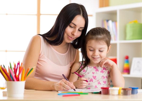 Une babysitter et une enfant écrivent en anglais