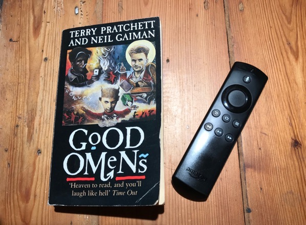 A copy of 'Good Omens' on a wooden floor, next to an Amazon Fire Stick remote control