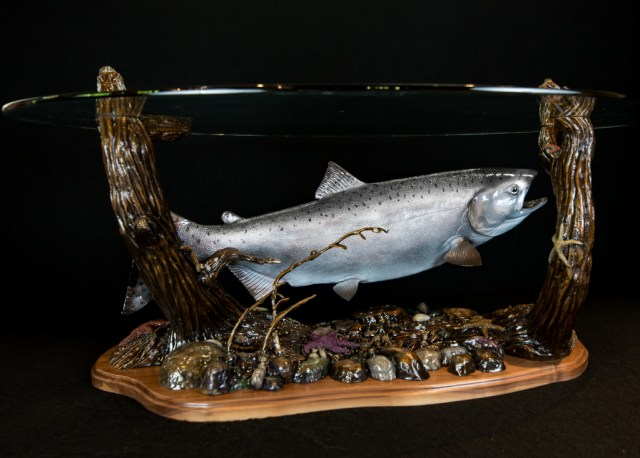 The bronze 'King Salmon Table' with a glass top with a king salmon and seabed below. (side view)