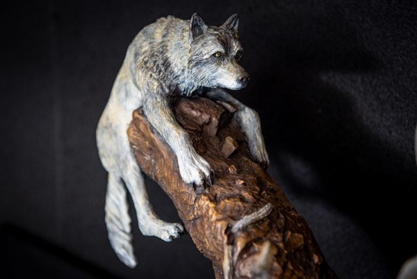 A wolf tries to gain purchase on a broken tree limb while chasing two rams in the bronze 'Leap of Faith'