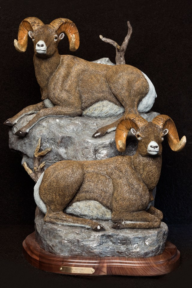 Bighorn sheep resting on rocks in the bronze 'The Bachelors' by Devin Roe.