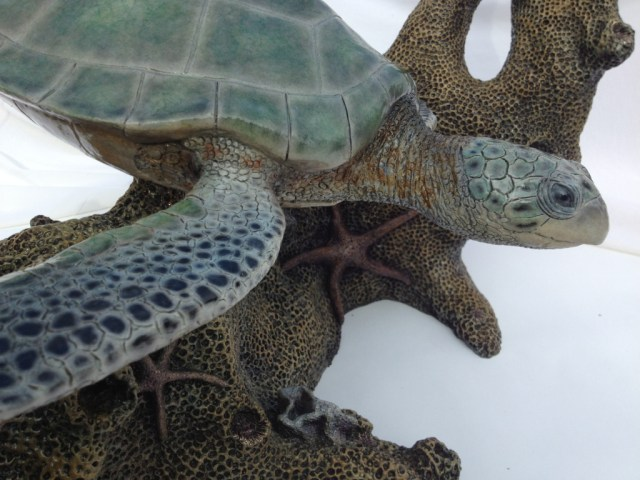"""A glass top table with a turtle and fish swimming amidst coral below in the bronze """"Turtle Table"""". (close-up side view)"""