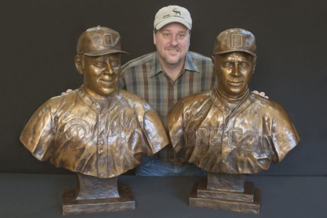 Artist Devin Rowe with his bronze sculpture of legendary University of Oregon baseball coaches.
