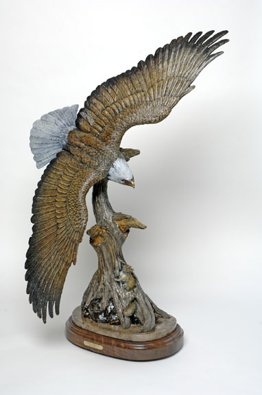 A bald eagle takes flight in the bronze sculpture 'The Hideout: Eagle' by Devin Rowe.